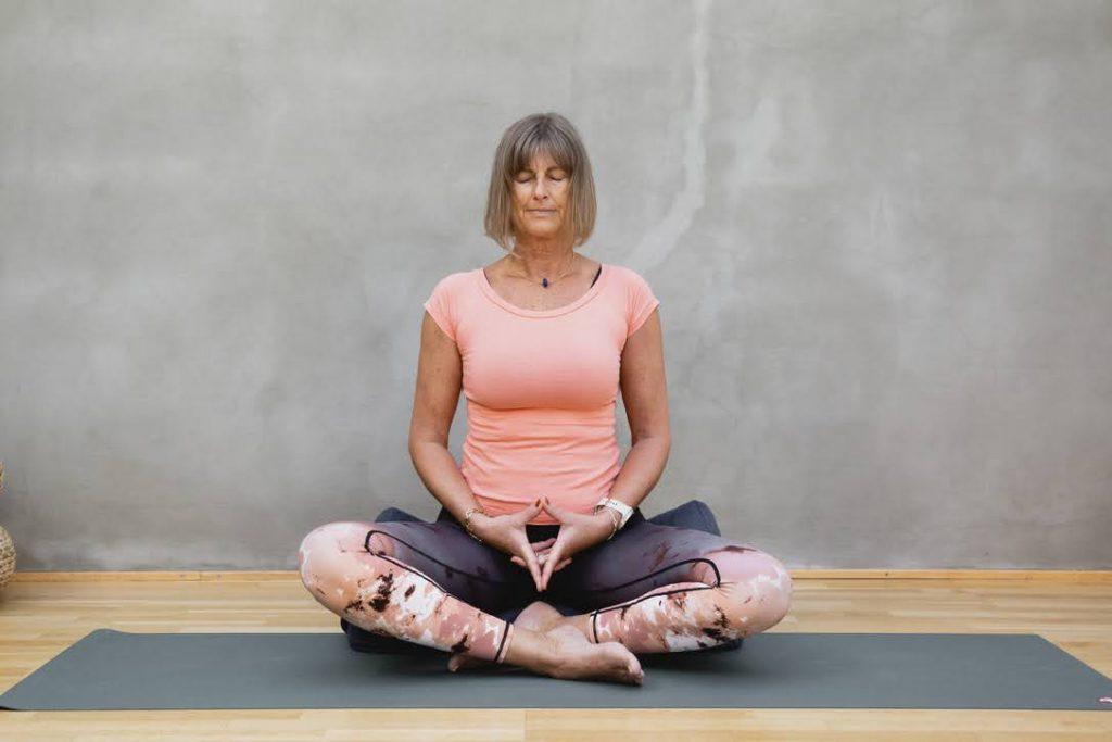 kvinne som sitter i lotus stilling på en yogamatte